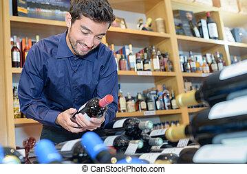 smiling customer buying bottle of wine at liquor store