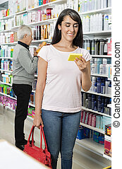 Smiling Customer Holding Product In Pharmacy