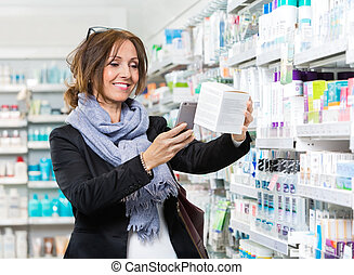 Smiling Customer Scanning Product Through Mobile Phone In...