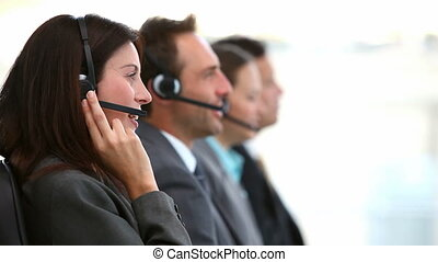 Smiling customer service agents working in a call center...