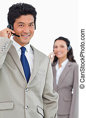 Smiling customer support employee with colleague behind him...