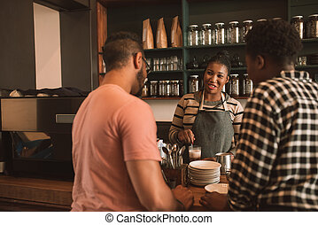 Smiling customers ordering coffee from a cafe barista