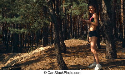 cute athletic girl stands near a tree in the forest and holds in her hand phone