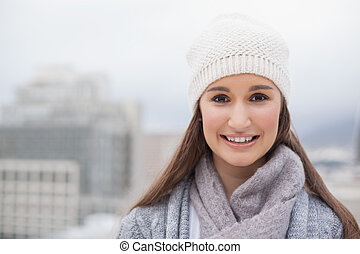 Smiling cute brunette with winter clothes on posing