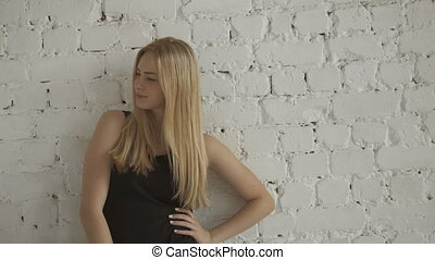 Smiling Cute Female Blonde Model Looking At Camera On  Brick Wall Background
