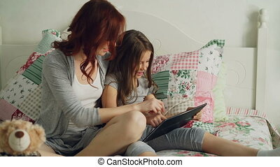 Smiling cute girl and her young mother laughing and using...