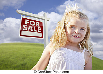 Smiling Cute Girl in Field with For Sale Real Estate Sign