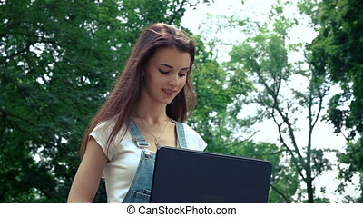 smiling cute girl looks in a laptop in the summer on the street sitting