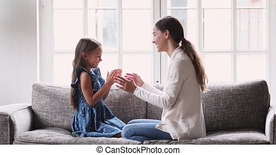 Smiling cute girl playing patty cake game with caring mother.