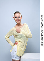 Smiling cute girl posing in yellow blouse