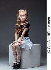 Smiling cute girl posing sitting on cube in studio