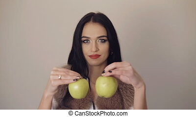 Smiling cute girl showing a juicy green apples to camera 4K.
