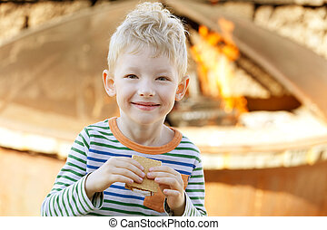 smiling cute little boy eating smores