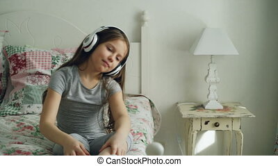 Smiling cute little girl in headphones dancing and moving her head funny while sitting in bed at home in cozy bedroom