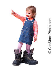 Smiling cute little girl in old big tracking shoes shows good-sign, isolated on white