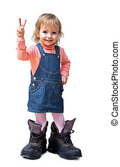 Smiling cute little girl in old big tracking shoes shows V-...
