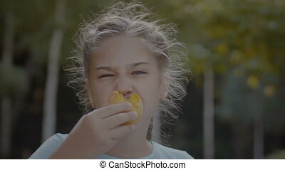 Smiling cute preteen girl eating peach outdoors - Smiling...