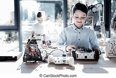 Smiling cute schoolboy working on his self moving robot