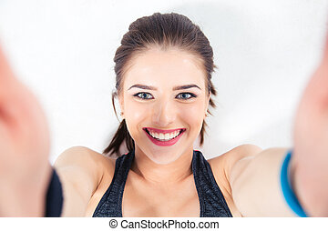 Smiling cute woman making selfie photo over gray background