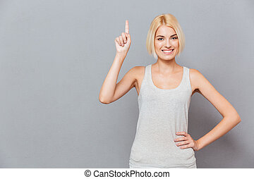 Smiling cute young woman pointing up