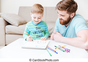 Smiling dad and little son drawing with colorful markers