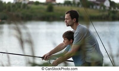 Smiling dad and son fishing and relaxing at pond