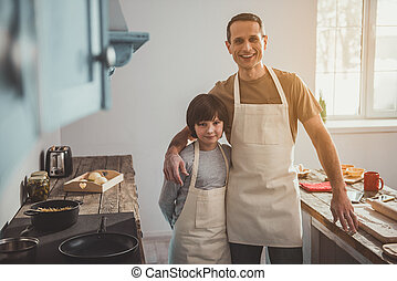 Smiling dad and son posing in aprons