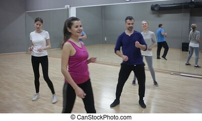 Smiling dancing people practicing bachata movements in dance studio for adults
