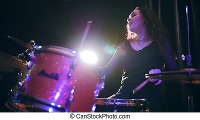 Smiling Dashing teen-girl with flowing hair percussion drummer performing with drums, slow motion