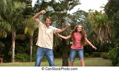 Smiling daughter jumping on a trampoline with her father in...