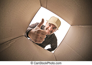 smiling delivery man view fron parcel inside