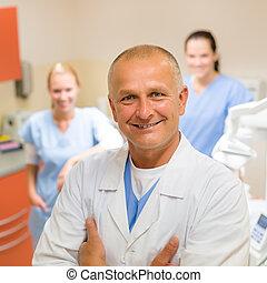 Smiling dental surgeon posing with nurses - Smiling male...