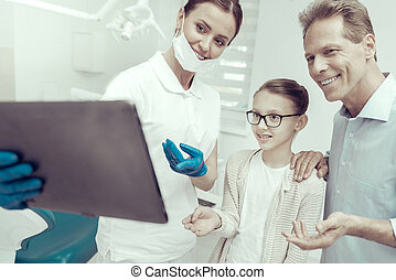 Smiling dentist looking at the screen of a tablet together with her patients