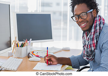 Smiling designer drawing something with a red pencil