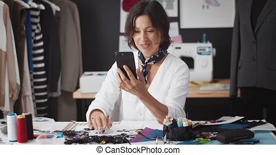 Smiling fashion designer with brown hair having video chat on smartphone while working at tailor studio. Concept of online communication and technology