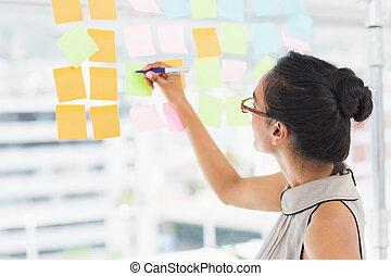 Smiling designer writing on sticky