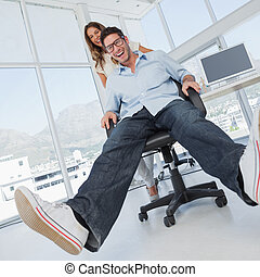 Smiling designers having fun with on a swivel chair in their...
