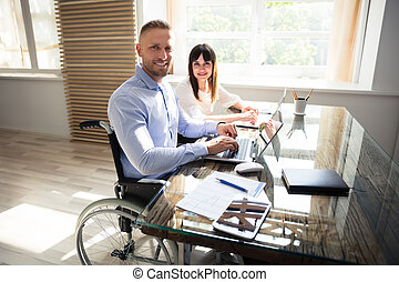 Smiling Disabled Businessman Working On Laptop