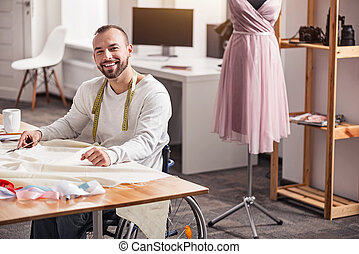Smiling disabled designer tailoring a dress