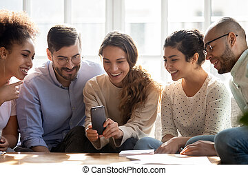 Smiling diverse friends using mobile phone, looking at screen