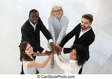 Smiling diverse team employees stack pile of hands top view