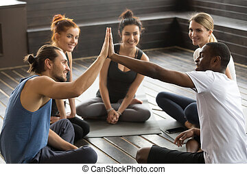 Smiling diverse yoga team members giving high-five at group trai