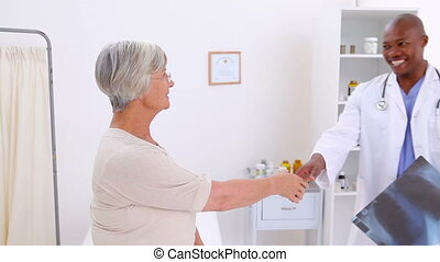 Smiling doctor and his patient shaking their hands in a...