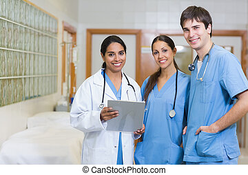 Smiling doctor and smiling male and female nurse in a hallway