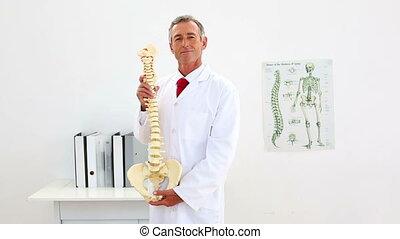 Smiling doctor explaining model of spine