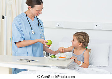 Smiling doctor giving apple to sick girl