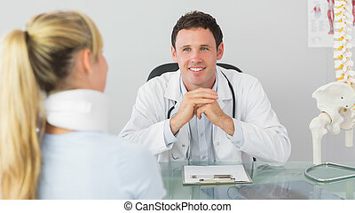 Smiling doctor having an appointment with a patient in...
