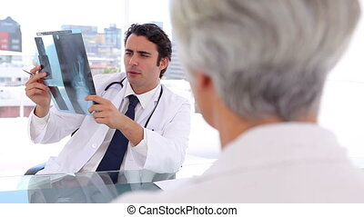 Smiling doctor holding an x-ray in front of his patient