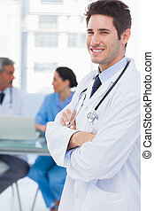 Smiling doctor looking at camera with colleagues behind