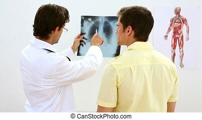 Smiling doctor looking at xray with patient in his office at...